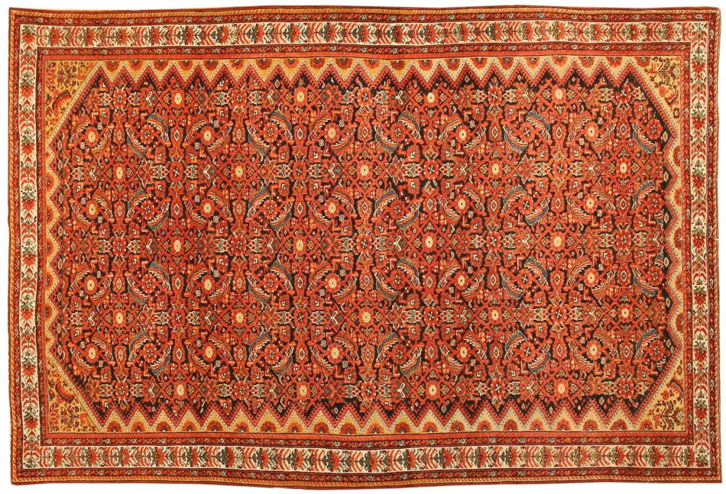 Sarouk tapijt, 191 x 132 cm. 'This dramatic carpet from the Farahan district features a characteristically dense Herati pattern in a Mina Khani-style arrangement that allows small amounts of the dark blue field to peek through. Multiple guardbands, taupe inner borders embellished with latchhook-pyramids and colorful border motifs set on neutral ground complete this richly-colored design.'