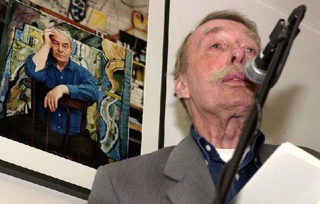 Kouwenaar met achter zich een foto van Lucebert